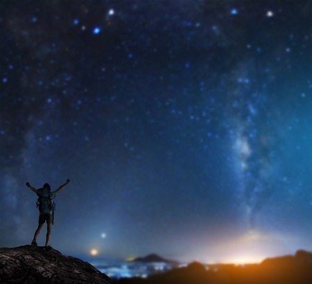 Hiker with backpack standing on top of the mountain with raised hands with starry sky on the background