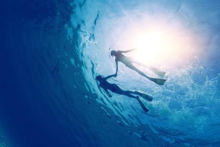 熱帯の海でシュノーケ リングのカップルの水中ビュー