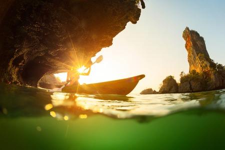 ocean kayak: Se�ora remando en kayak en el mar tropical cerca de la roca con la parte bajo el agua