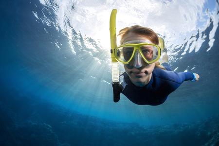 노란색 마스크에 숙녀 freediver의 수중 총을 닫습니다