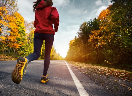 Lady running on the asphalt road through the autumn forest Stock Photo