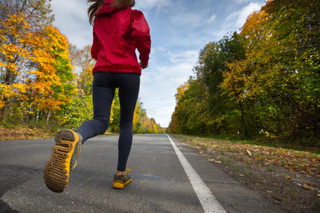 successful woman: Lady running on the asphalt road through the autumn forest Stock Photo