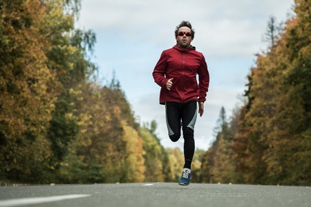 exertion: Young man athlete running hard on the asphalt road in the autumn forest