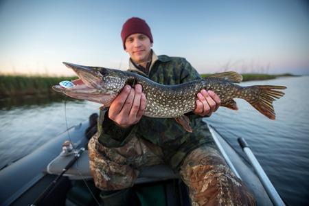 pescador: Pescador joven feliz que sostiene el lucio y sentado en la barca en el lago