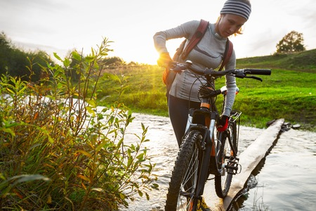 road cycling: Lady with bicycle crossing the river at sunset