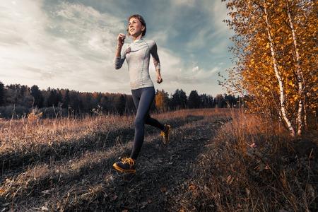 running: Señora Delgado se ejecuta en el bosque de otoño Foto de archivo