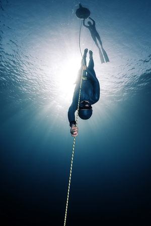 immersion: Lady free diver descending along the rope linked to the buoy on surface. Free immersion discipline