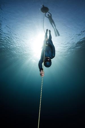 表面のブイにロープに沿って降順女性フリーダイバーがリンクされています。無料浸漬規律