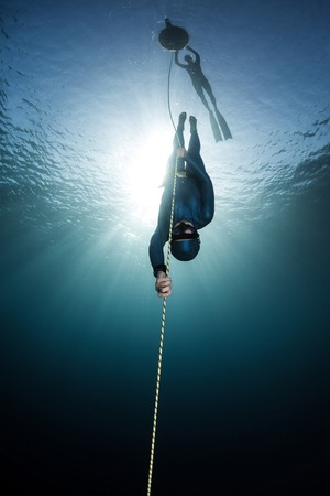 Lady free diver descending along the rope linked to the buoy on surface. Free immersion discipline