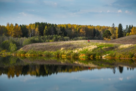 off road biking: Lady cycling (remote red spot) on the autumn meadow near the lake at sunny day Stock Photo