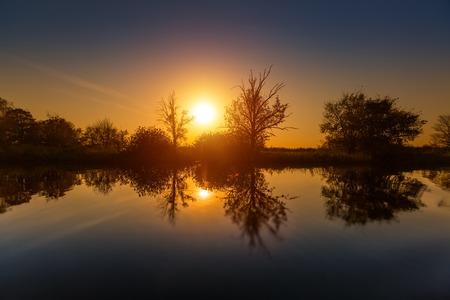lake sunset: Calm lake with autumn trees on the coast at sunset Stock Photo