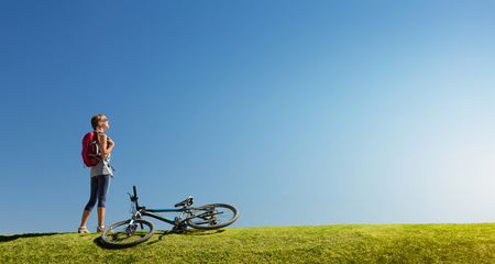 grass and sky: Young lady standing near bicycle on the green grass meadow at sunny day Stock Photo