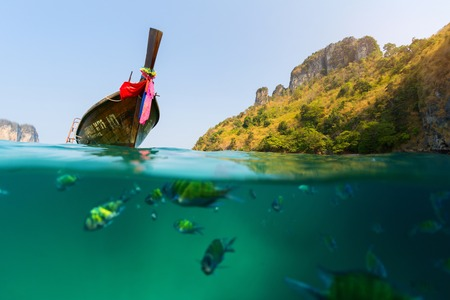 ocean water: Split shot with fish underwater and traditional wooden boat on the surface at sunny day Stock Photo