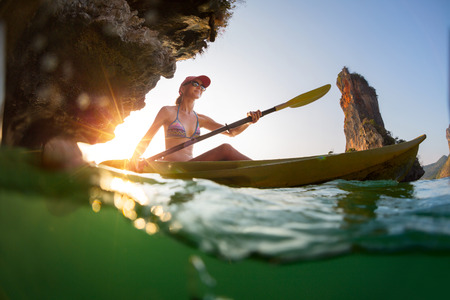 Giovane donna che rema il kayak in una baia con montagne calcaree. Colpo spaccato con vista subacquea Archivio Fotografico - 47379699