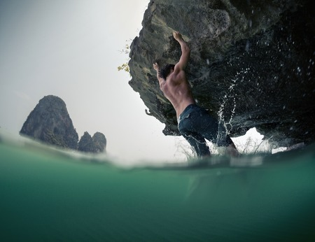 railey: Young man trying to climb natural wall without belay. Deep water soloing. Stock Photo