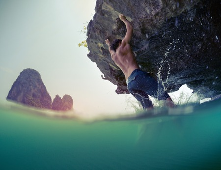 railey: Young athlete trying to climb natural wall without belay. Deep water soloing. Stock Photo