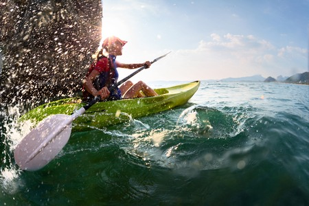 ocean kayak: Jovencita remando con fuerza el kayak con un mont�n de salpicaduras cerca de los acantilados en d�a soleado