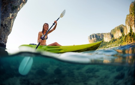 Giovane donna che rema il kayak in una baia con montagne calcaree. Colpo spaccato con vista subacquea Archivio Fotografico - 47381384