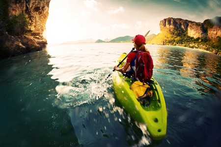 ocean kayak: Jovencita remar el kayak en una tranquila bah�a con las monta�as de piedra caliza
