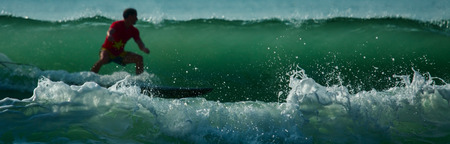 foreground focus: Surfer riding the wave at sunny day. Focus on the breaking wave on foreground