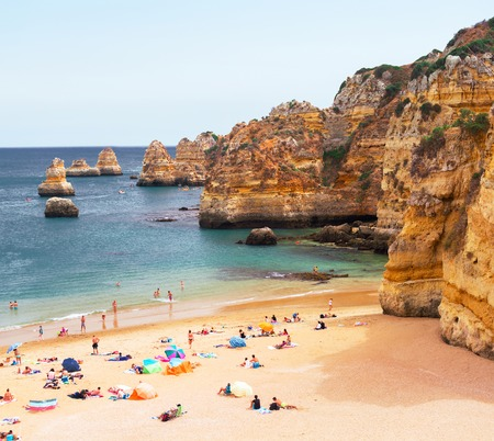 Lagos: People relaxing on the beach surrounded by mountains, Lagos, Portugal
