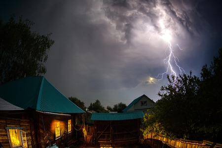 Thunderbolt over houses in the village at night