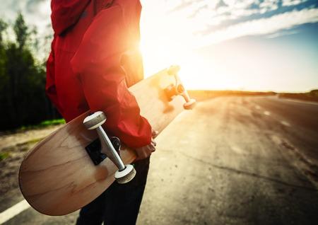 Persoon met skateboard staande op de weg Stockfoto