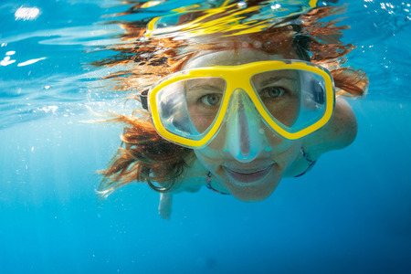 Close up shot of the young lady snorkeling in the clear tropical sea