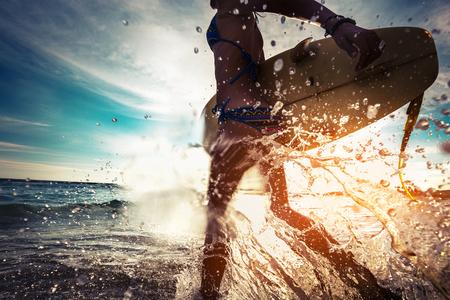 mojada: Señora con la tabla hawaiana corriendo en el mar con una gran cantidad de salpicaduras Foto de archivo