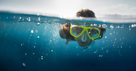 split up: Close up split shot of the young lady snorkeling in the clear tropical sea