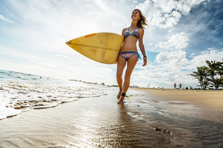 girl action: Lady walking with surfboard along the tropical beach Stock Photo