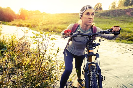 off road biking: Lady with bicycle crossing the river with green coasts at sunset