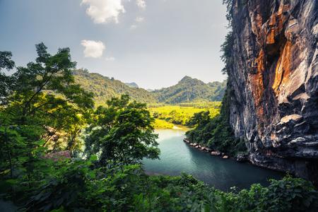 dia soleado: Río claro que fluye de la cueva en el Parque Nacional de Phong Nha, Vietnam