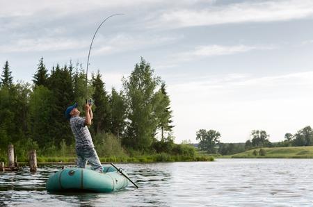 pecheur: Le pêcheur à la tige dans le bateau sur l'étang calme