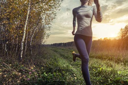 秋の森の中を実行している女性