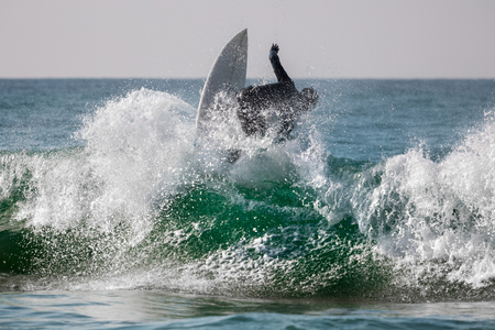 sea wave: Surfing riding the wave with lots of splashes Stock Photo