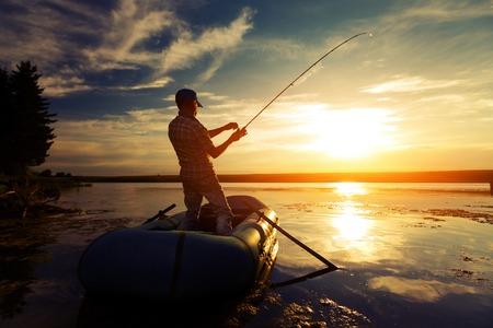 Visser met hengel in de boot op de kalme vijver bij zonsondergang