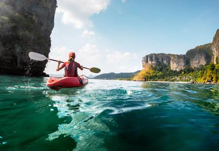 ocean kayak: Señora remar el kayak en la bahía tropical calma al atardecer Foto de archivo