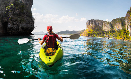 canoe: Lady paddling the kayak in the calm tropical bay