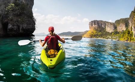 Lady pagaiare il kayak nella calma baia tropicale