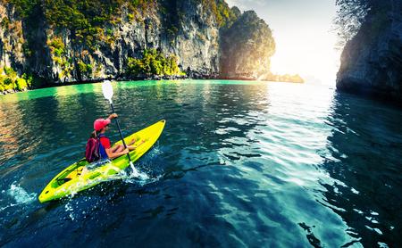 Lady pagaiare il kayak nella calma baia tropicale Archivio Fotografico - 47383510