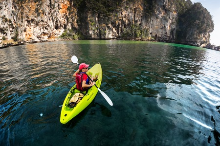 outdoor activities: Lady paddling the kayak in the calm tropical bay