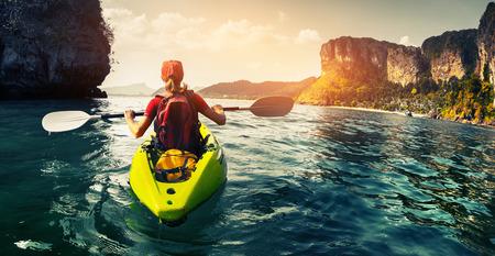 ocean kayak: Se�ora remar el kayak en la bah�a tropical calma al atardecer Foto de archivo