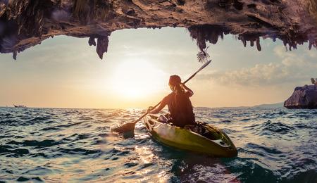 ocean kayak: Se�ora remar el kayak en el mar agitado al atardecer