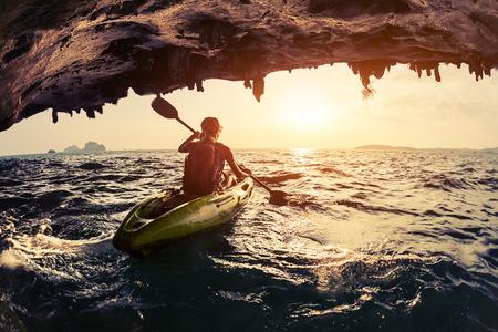 mare agitato: Lady pagaiare il kayak in mare agitato al tramonto