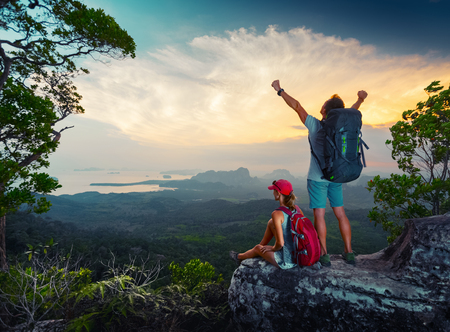 freedom: Two hikers relaxing on top of the mountain and enjoying sunset valley view