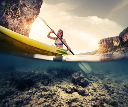 cave exploring: Split shot of the lady paddling the kayak in the calm tropical sea with underwater view of the bottom Stock Photo