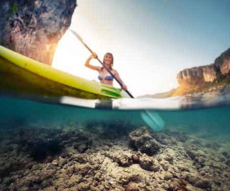 ocean kayak: Tiro partido de la dama de remar el kayak en el mar tropical tranquilo con vista bajo el agua de la parte inferior. Centrarse s�lo en la parte inferior. Foto de archivo