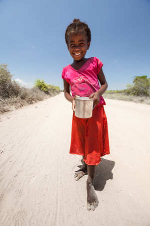 shoeless: MORONDAVA, MADAGASCAR - DECEMBER 08 Portrait of unidentified smiling girl with can, December 08, 2013, Morondava region, Madagascar. Children in Madagascar are friendly and often barefoot.