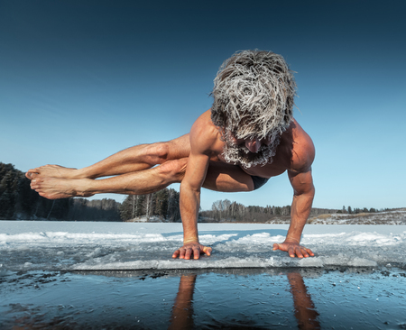 wild hair: Man doing yoga exercise (parsva bakasana) on the ice of frozen lake